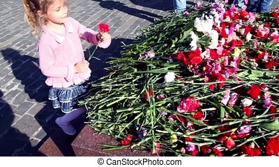 Little girl walk and lay flower at sunny day, people walk...