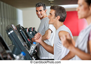 Man Running On Treadmill In Fitness Club - Portrait of happy...