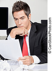 Thoughtful Businessman Reading Document In Office -...