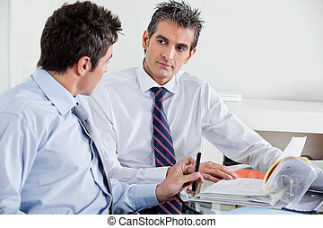 Businessmen Discussing Paperwork In Office