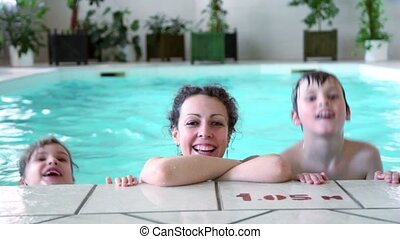 Mother with two kids boy and girl smile at pool edge -...