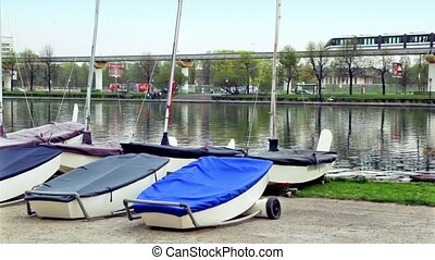 Several boats lay near pond, train and city traffic on...