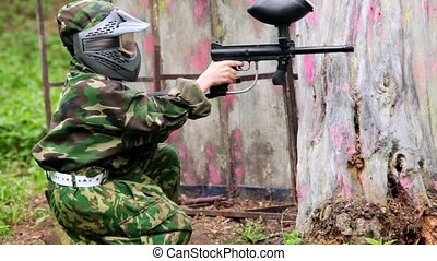 Boy paintball player sits with gun in ambush near tree - Boy...