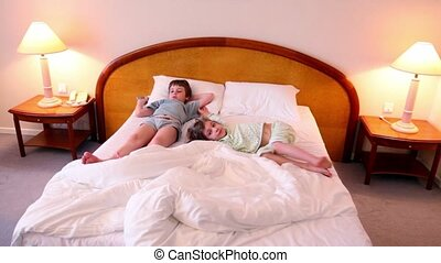 Two kids boy and girl lay on bed in different poses and watch tv