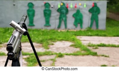 Paintball gun and targets in outdoor shooting gallery, shown...