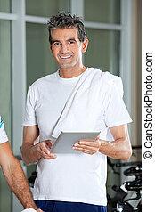 Man Using Digital Tablet In Health Club - Portrait of happy...