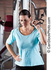 Woman Working Out In Health Club - Mature woman working out...