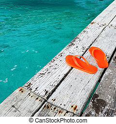 Sandals at jetty by the sea