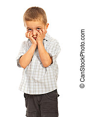 Worried small boy holding hands to face isolated on white...