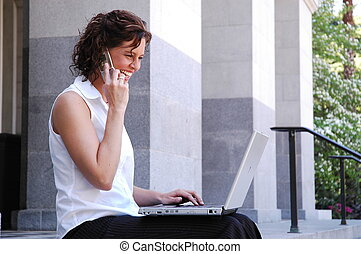 mobile business woman talking on cell phone and working on...
