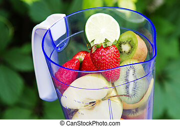 Electric blender with fruits in it, green leaves background