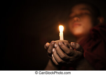 Novice with candlelight - Young novice monk holding a...