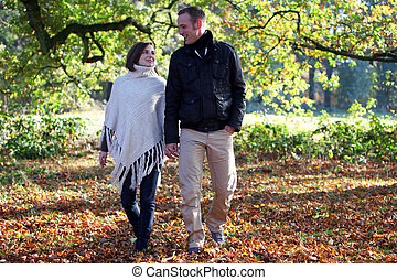 Young couple strolling through woodland - Fashionable...