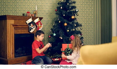 Christmas wonder - Children opening their gifts under a...
