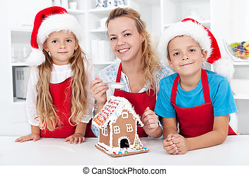 Family at christmas making a gingerbread cookie house
