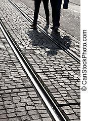 Man and Woman Cross Tram Track in Geneva, Switzerland, Europe