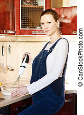 Young pregnant woman in kitchen making a food