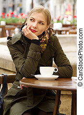 Beautiful woman drinking coffee in outdoor cafe