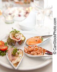 Fancy appetizers with seafood and fine ham on silver spoons