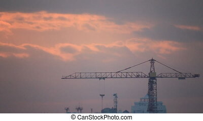 Crane on building site on the orange clouds background