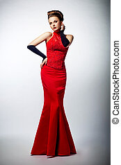 Tempting sexy slim female in sensual red long dress posing -...