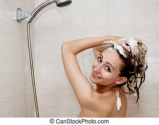 young brunette woman is taking shower and washing hair