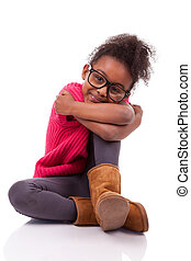Cute young African American girl seated on the floor -...