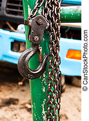 Hook the chain. - Large metal hook and chains attached to a...