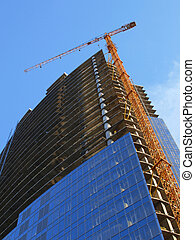 building under construction - A crane and skyscraper...