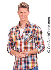 attractive young casual man welcoming with hands together and big smile over white background