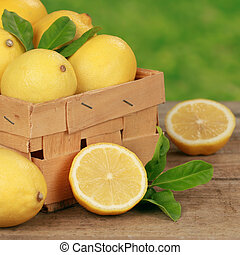 Lemons with lemon leaves in a wooden box on a table with...