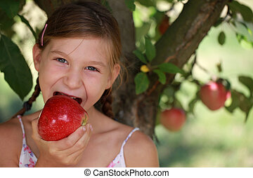 Young girl eating an apple under an apple tree Shallow depth...