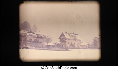 Vintage 8mm. Snowy neighbourhood field, with people walking...