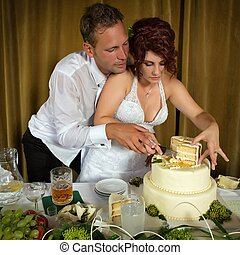 cutting the wedding cake - Bride and Groom Cutting the...