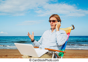 Business man on the beach - Business man sitting and working...