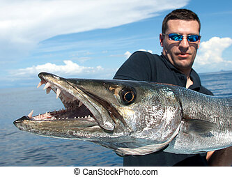 The giant barracuda - lucky fisherman holding a giant...