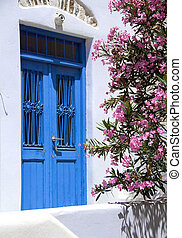 greek island ancient building door with flowers - old greek...