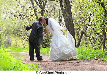 bride and groom kissing in the park