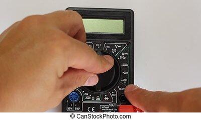 Man measures digital multimeter
