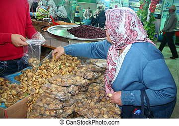 old lady on shopping - Old lady while buying dried fig at...