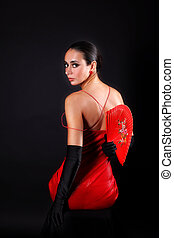woman with fan in red outfit against black background -...