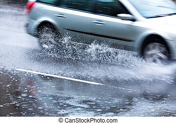 Car in a downpour - Car driving through a large puddle in a...