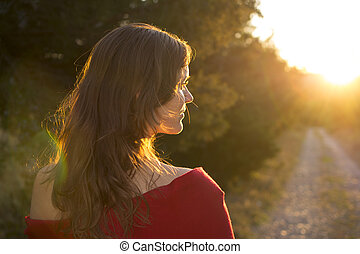 Towards the light - Beautiful young girl walking on a...