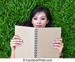 Woman lying on grass with a book - Woman lying on green...
