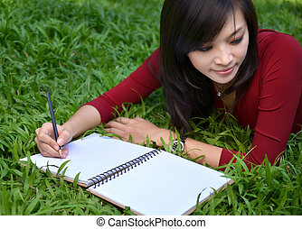 pretty women writing book - pretty women lying on green...