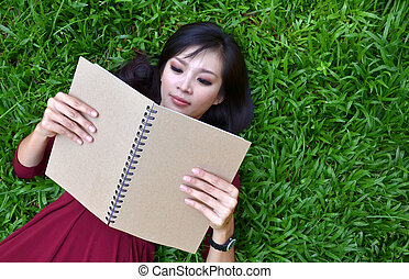 Woman lying on green grass with book - Woman lying on green...