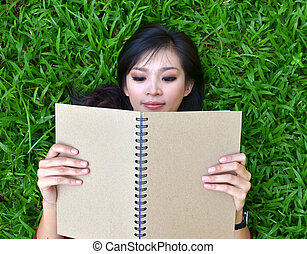 Woman lying on grass with book - Woman lying on grass with a...
