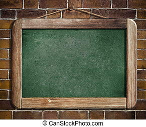 Aged green blackboard hanging on brick wall as a background...