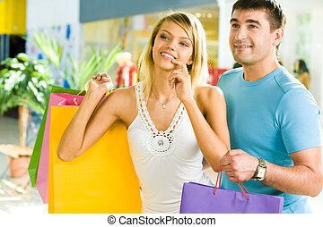 Choosing presents - Portrait of happy couple standing in the...