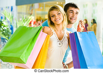 Shopping together - Portrait of smiling man embracing young...